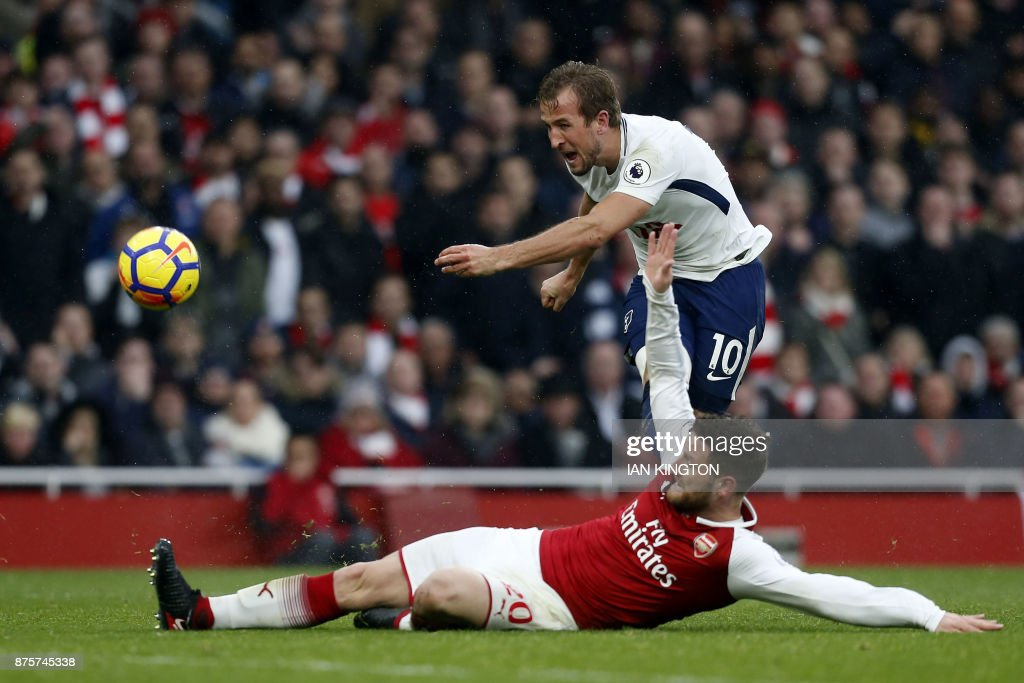 TOPSHOT - Arsenal's German defender Shkodran Mustafi (bottom) blocks a shot by England's striker Harry Kane during the English Premier League football match between Arsenal and Tottenham Hotspur at the Emirates Stadium in London on November 18, 2017. / AFP PHOTO / IKIMAGES / Ian KINGTON / RESTRICTED TO EDITORIAL USE. No use with unauthorized audio, video, data, fixture lists, club/league logos or 'live' services. Online in-match use limited to 45 images, no video emulation. No use in betting, games or single club/league/player publications. /