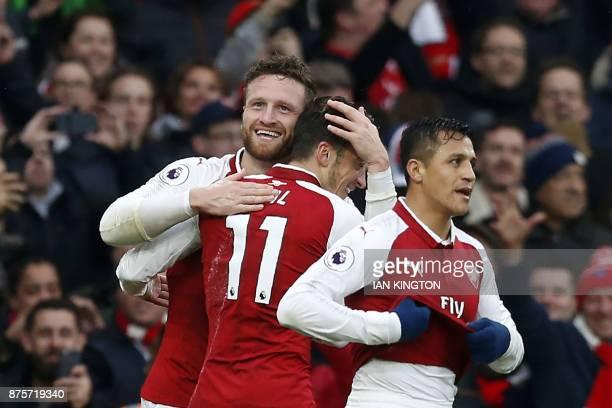 Arsenal's German defender Shkodran Mustafi celebrates scoring the team's first goal with Arsenal's Chilean striker Alexis Sanchez and Arsenal's...