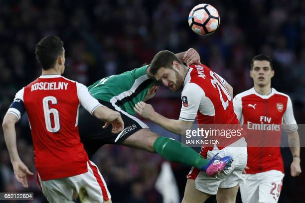 Arsenal's German defender Shkodran Mustafi is hurt in this clash with Lincoln City's English striker Matt Rhead during the English FA cup quarter...