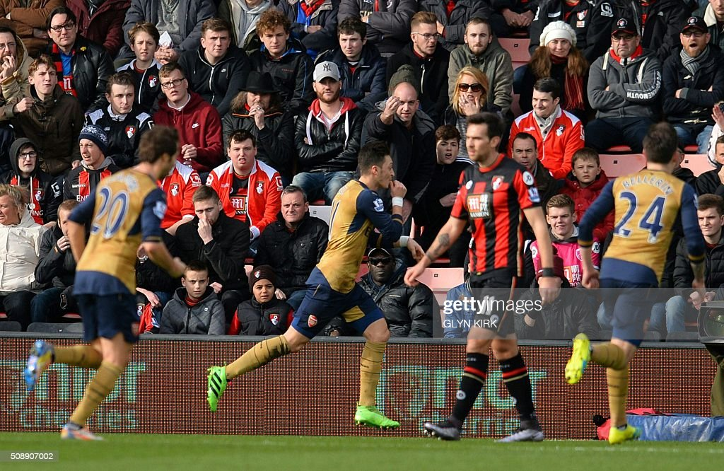 Arsenal's German midfielder Mesut Ozil (C) celebrates scoring his team's first goal during the English Premier League football match between Bournemouth and Arsenal at the Vitality Stadium in Bournemouth, southern England on February 7, 2016. / AFP / GLYN KIRK / RESTRICTED TO EDITORIAL USE. No use with unauthorized audio, video, data, fixture lists, club/league logos or 'live' services. Online in-match use limited to 75 images, no video emulation. No use in betting, games or single club/league/player publications. /