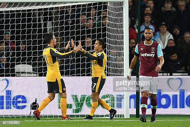 Arsenal's German midfielder Mesut Ozil celebrates with Arsenal's Chilean striker Alexis Sanchez after scoring the opening goal of the English Premier...