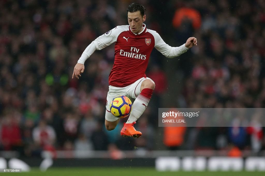 TOPSHOT - Arsenal's German midfielder Mesut Ozil controls the ball during the English Premier League football match between Arsenal and Tottenham Hotspur at the Emirates Stadium in London on November 18, 2017. / AFP PHOTO / Daniel LEAL-OLIVAS / RESTRICTED TO EDITORIAL USE. No use with unauthorized audio, video, data, fixture lists, club/league logos or 'live' services. Online in-match use limited to 75 images, no video emulation. No use in betting, games or single club/league/player publications. /