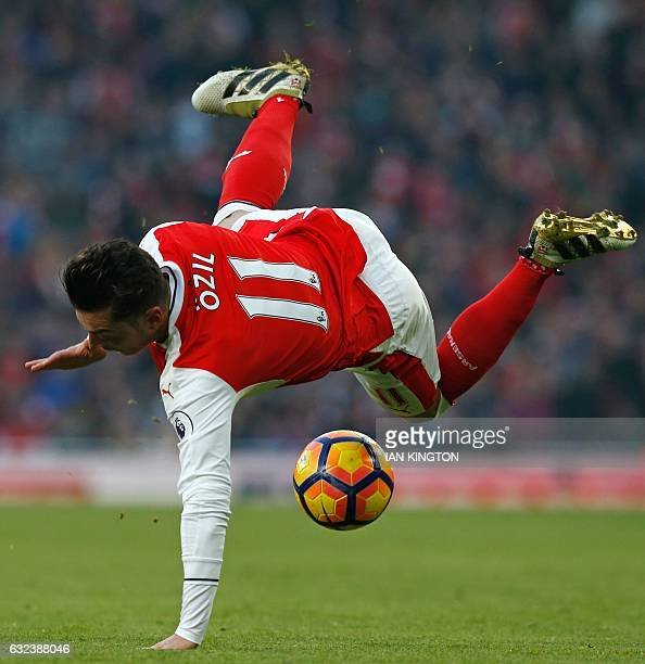 TOPSHOT Arsenal's German midfielder Mesut Ozil is tackled by Burnley's English midfielder Dean Marney during the English Premier League football...