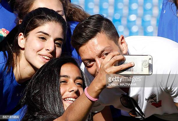 Arsenal's German midfielder Mesut Ozil poses for pictures during a training session of the women's U17 Jordanian national football team on May 18...