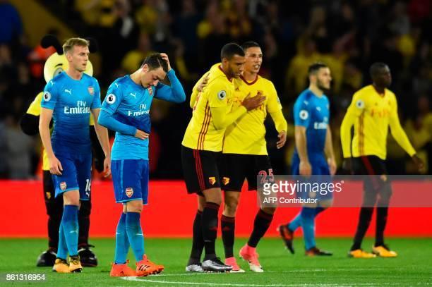 Arsenal's German midfielder Mesut Ozil reacts at the final whistle as Watford's English striker Troy Deeney and Watford's Germanborn Greek midfielder...