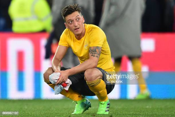 Arsenal's German midfielder Mesut Ozil reacts to their defeat on the pitch after the English Premier League football match between Crystal Palace and...