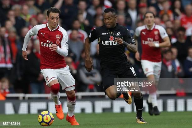 Arsenal's German midfielder Mesut Ozil runs away from Swansea City's Ghanaian striker Jordan Ayew during the English Premier League football match...