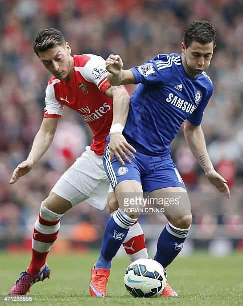 Arsenal's German midfielder Mesut Ozil vies with Chelsea's Belgian midfielder Eden Hazard during the English Premier League football match between...