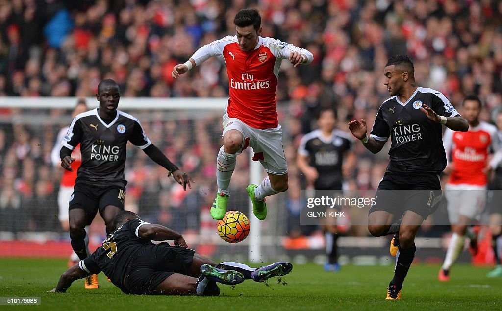 Arsenal's German midfielder Mesut Ozil (C) vies with Leicester City's French midfielder N'Golo Kante (L) Leicester City's English defender Wes Morgan (2L) and Leicester City's English defender Danny Simpson during the English Premier League football match between Arsenal and Leicester at the Emirates Stadium in London on February 14, 2016. / AFP / GLYN KIRK / RESTRICTED TO EDITORIAL USE. No use with unauthorized audio, video, data, fixture lists, club/league logos or 'live' services. Online in-match use limited to 75 images, no video emulation. No use in betting, games or single club/league/player publications. /