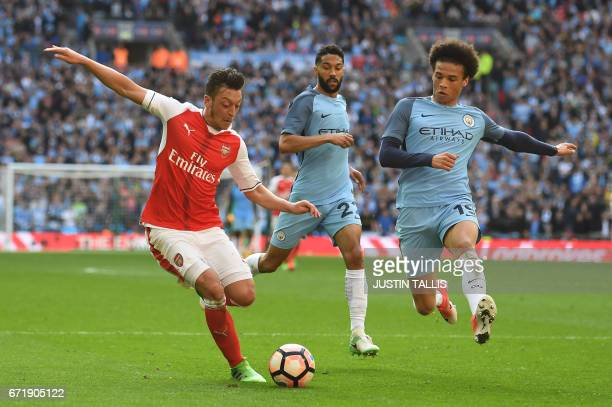 Arsenal's German midfielder Mesut Ozil vies with Manchester City's German midfielder Leroy Sane during the FA Cup semifinal football match between...