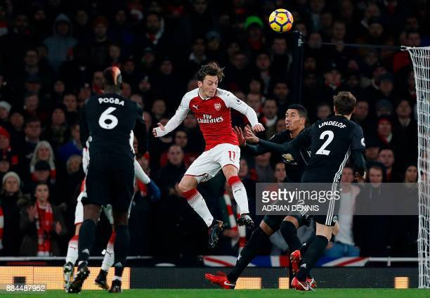 Arsenal's German midfielder Mesut Ozil vies with Manchester United's French midfielder Paul Pogba and Manchester United's Swedish defender Victor...