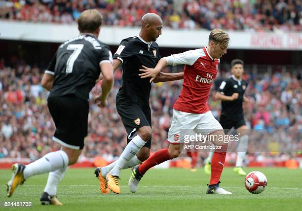 Arsenal's German midfielder Mesut Ozil vies with Sevilla's Steven N'Zonzi during the preseason friendly football match between Arsenal and Sevilla at...