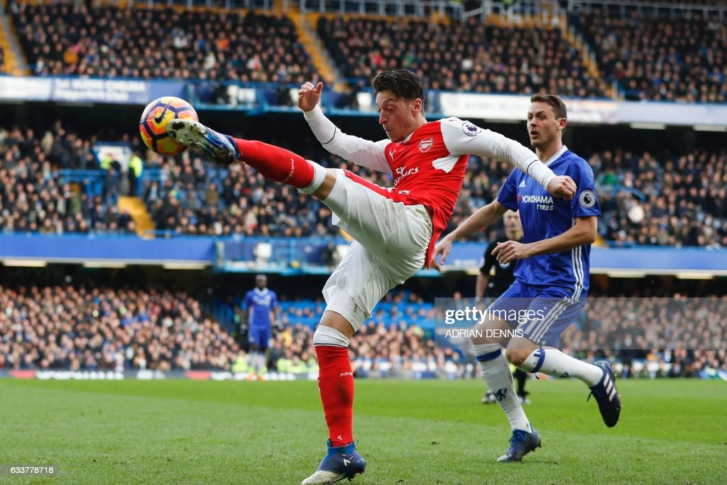 TOPSHOT - Arsenal's German midfielder Mesut Ozil vollies the ball during the English Premier League football match between Chelsea and Arsenal at Stamford Bridge in London on February 4, 2017. / AFP / Adrian DENNIS / RESTRICTED TO EDITORIAL USE. No use with unauthorized audio, video, data, fixture lists, club/league logos or 'live' services. Online in-match use limited to 75 images, no video emulation. No use in betting, games or single club/league/player publications. /