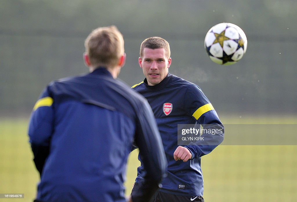Arsenal's German striker Lukas Podolski (R) and German defender Per Mertesacker (L) are seen training for the forthcoming UEFA Champions League round of 16 football match against Bayern Munich at Arsenal's training ground, London Colney, North London, England on February 18, 2013.