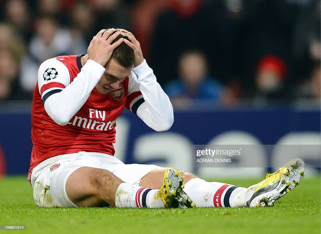 Arsenal's German striker Lukas Podolski reacts after missing a chance on goal during the UEFA Champions League group B football match against Montpellier at the Emirates Stadium, North London on November 21, 2012. AFP PHOTO / ADRIAN DENNIS