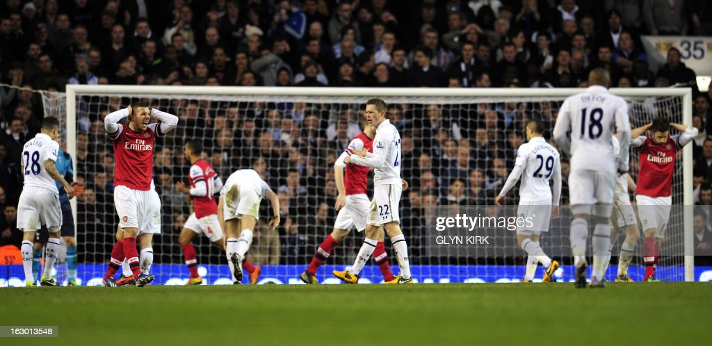 "Arsenal's German striker Lukas Podolski (L) reacts to a missed chance on a goal during the English Premier League football match between Tottenham Hotspur and Arsenal at White Hart Lane in north London on March 3, 2013. Tottenham Hotspur won the match 2-1. USE. No use with unauthorized audio, video, data, fixture lists, club/league logos or ""live"" services. Online in-match use limited to 45 images, no video emulation. No use in betting, games or single club/league/player publications"