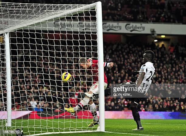 Arsenal's German striker Lukas Podolski scores their third goal as Newcastle United's Ivorian midfielder Cheick Tiote tries to block during the...