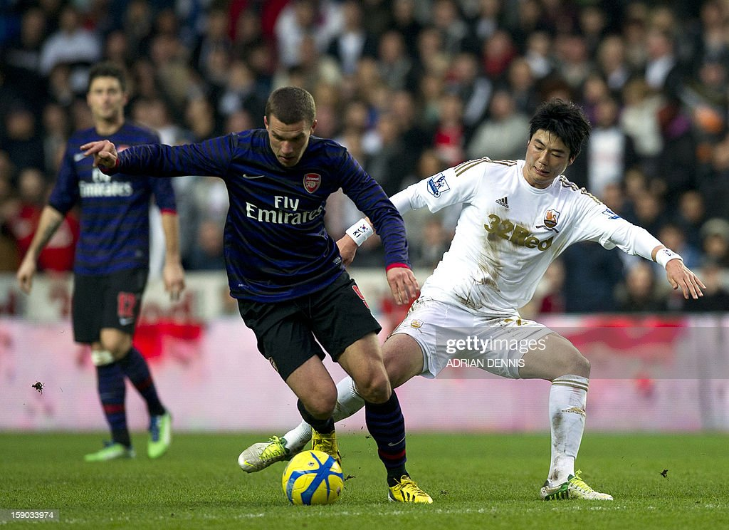 """Arsenal's German striker Lukas Podolski (C) vies for the ball against Swansea City's South Korean midfielder Ki Sung-Yueng (R) during the FA Cup third round football match at the Liberty Stadium in Swansea, Wales, on January 6, 2013. The game ended with a 2-2 draw. USE. No use with unauthorized audio, video, data, fixture lists, club/league logos or """"live"""" services. Online in-match use limited to 45 images, no video emulation. No use in betting, games or single club/league/player publications"""