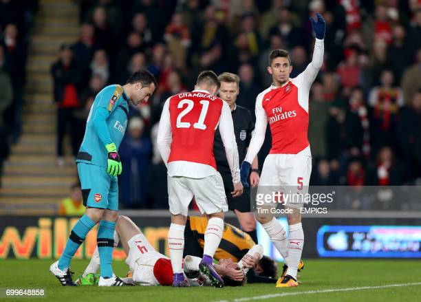 Arsenal's goalkeeper David Ospina Calum Chambers and Gabriel Paulista react as Per Mertesacker collides with Hull Citys Nick Powell
