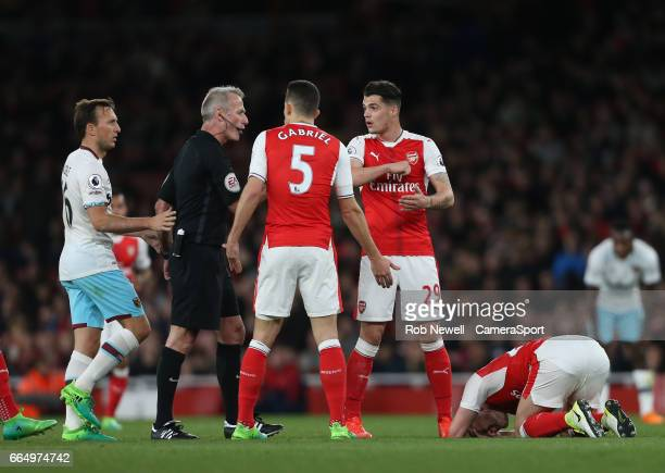 Arsenal's Granit Xhaka accuses West Ham United's Andy Carroll of an elbow on Shkodran Mustafi during the Premier League match between Arsenal and...
