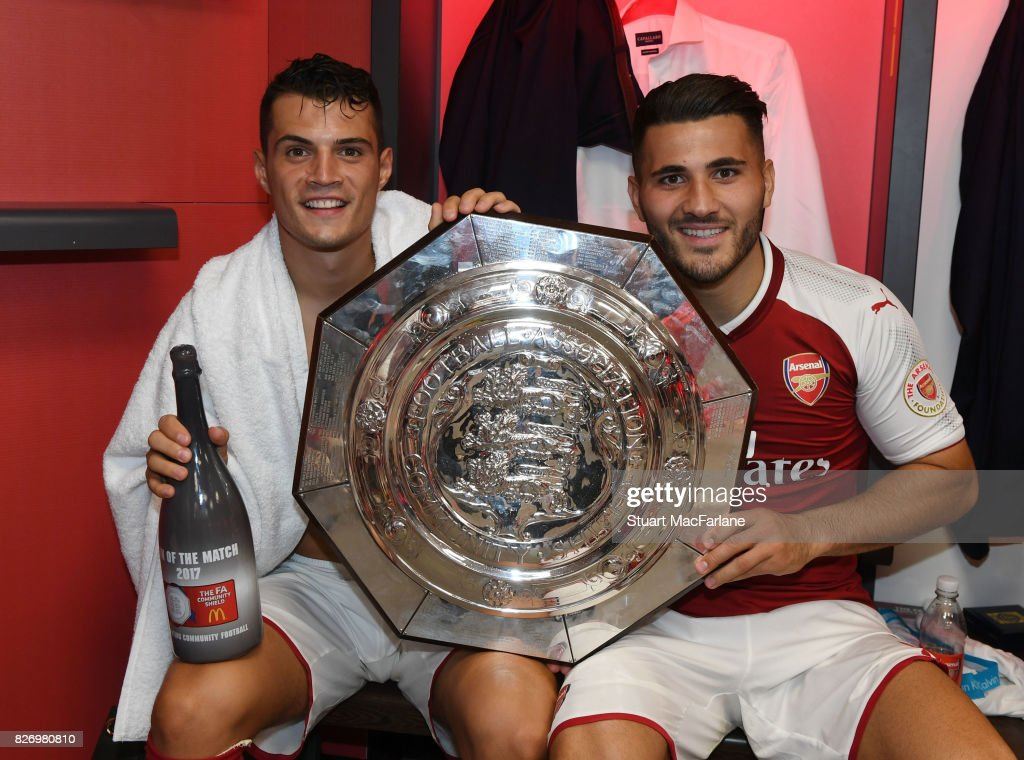 Arsenal's Granit Xhaka and Sead Kolasinac with the Community shield in the changing room after the FA Community Shield match between Chelsea and Arsenal at Wembley Stadium on August 6, 2017 in London, England.