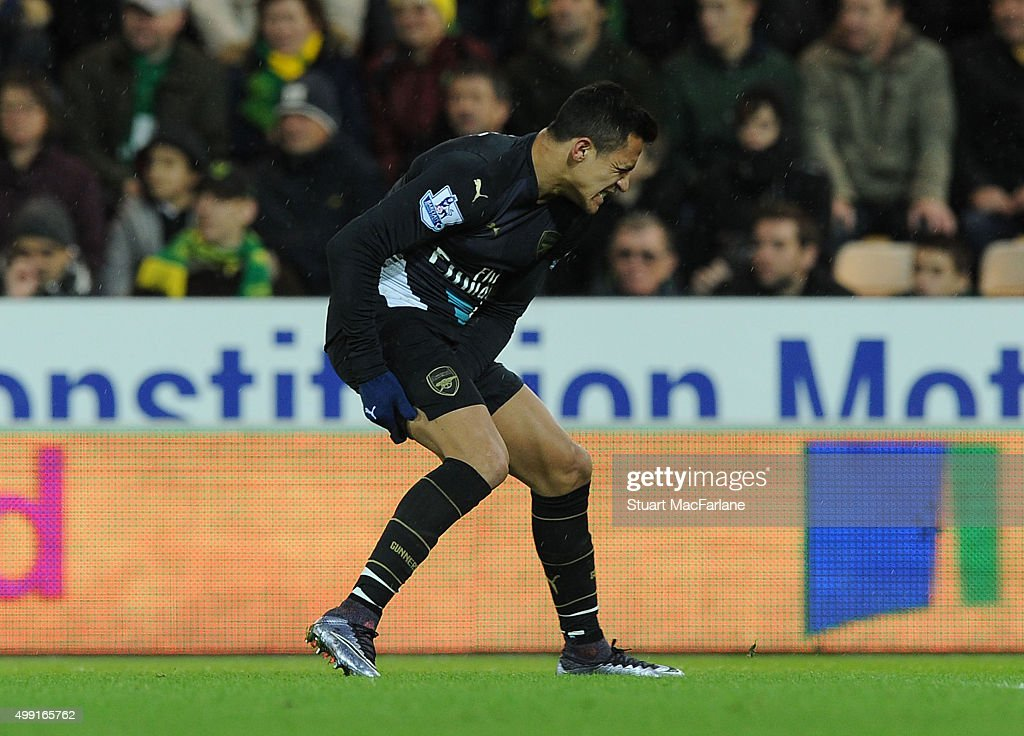 Arsenal's injured striker Alexis Sanchez holds his hamstring during the Barclays Premier League match between Norwich City and Arsenal at Carrow Road on November 29, 2015 in Norwich, England.