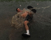 Arsenal's Jack Wilshere enjoying the wet conditions after a training session on July 30 2014 in Bad Waltersdorf Austria