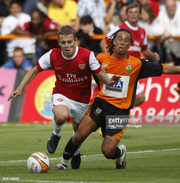 Arsenal's Jack Wilshere skips over challenge from Barnet's Sam Cox during the preseason friendly match at Underhill London