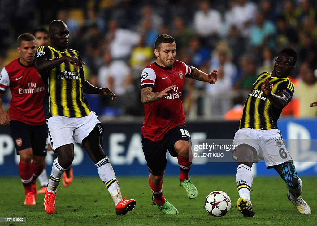 Arsenal's Jack Wilshere (2R) vies for the ball with Fenerbahce's Joseph Yobo (R) during their UEFA Champions League Play Off first leg match at Sukru Saracoglu Stadium in Istanbul on August 21, 2013. AFP PHOTO/BULENT KILIC