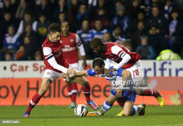 Arsenal's Johan Djourou and Laurent Koscielny battle for the ball with Reading's Noel Hunt