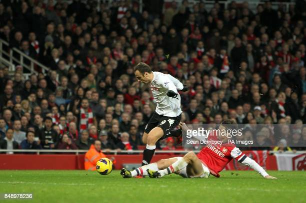 Arsenal's Laurent Koscielny and Fulham's Dimitar Berbatov battle for the ball