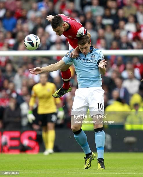 Arsenal's Laurent Koscielny and Manchester City's Edin Dzeko battle for the ball