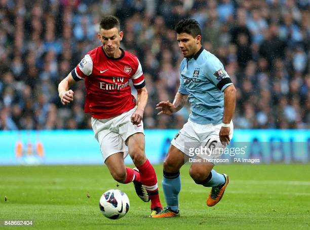 Arsenal's Laurent Koscielny and Manchester City's Sergio Aguero battle for the ball during the Barclays Premier League match at the Etihad Stadium...