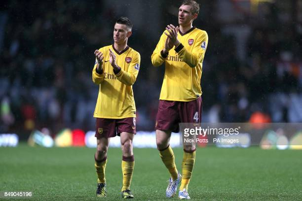 Arsenal's Laurent Koscielny and Per Mertesacker applaud the fans as they walk off together after the final whistle