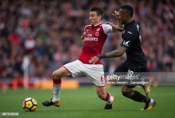 Arsenal's Laurent Koscielny holds off the challenge from Swansea City's Jordan Ayew during the Premier League match between Arsenal and Swansea City...