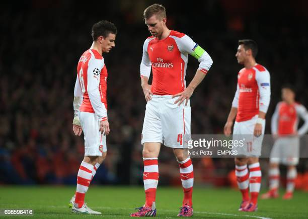 Arsenal's Laurent Koscielny Per Mertesacker and Mesut Ozil stand dejected after conceding their first goal of the game