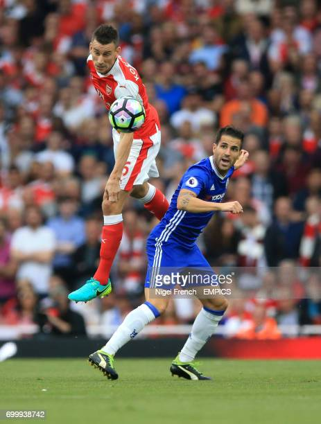 Arsenal's Laurent Koscielny wins the ball ahead of Chelsea's Cesc Fabregas