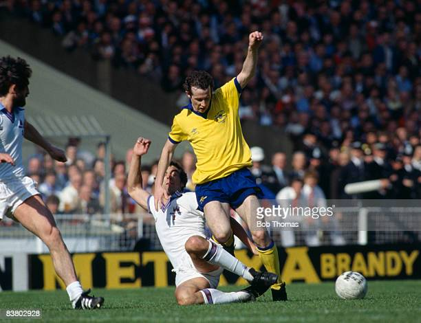 Arsenal's Liam Brady is tackled by West Ham United goalscorer Trevor Brooking during the FA Cup Final at Wembley Stadium 10th May 1980 West Ham...