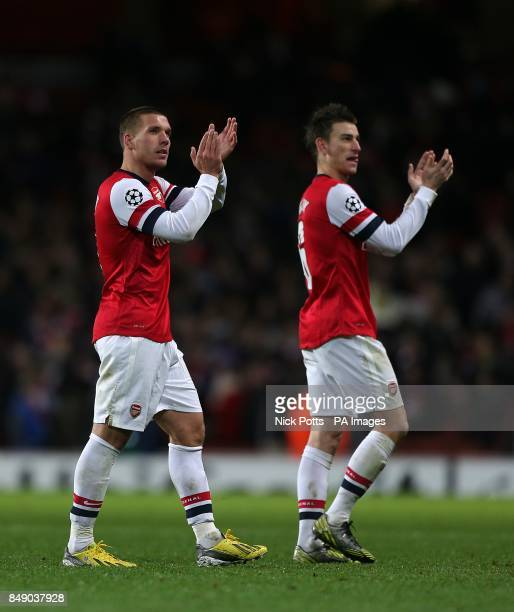 Arsenal's Lukas Podolski and Laurent Koscielny applaud the fans after the game
