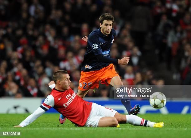 Arsenal's Lukas Podolski slides in to challenge Montpellier's Mathieu Deplagne