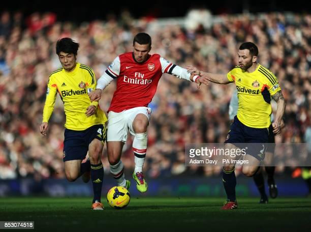 Arsenal's Lukas Podolski with Sunderland's Ki SungYueng and Phil Bardsley during the Barclays Premier League match at the Emirates Stadium London