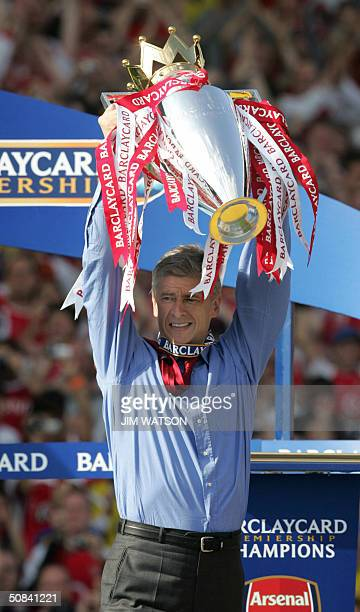 Arsenal's manager Arsene Wenger holds up the Premiership trophy after winning the Premiership title and defeating Leicsester City 15 May 2004 at...