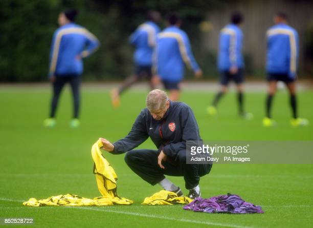 Arsenal's Manager Arsene Wenger sorts through the bibs during a training session at London Colney St Albans