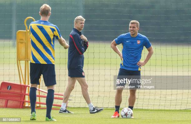 Arsenal's manager Arsene Wenger watches over Lukas Podolski right and Per Mertesacker during a training session at London Colney St Albans