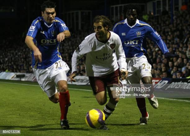 Arsenal's Mathieu Flamini battles for the ball with Portsmouth's Richard Hughes and Benjani Mwaruwari