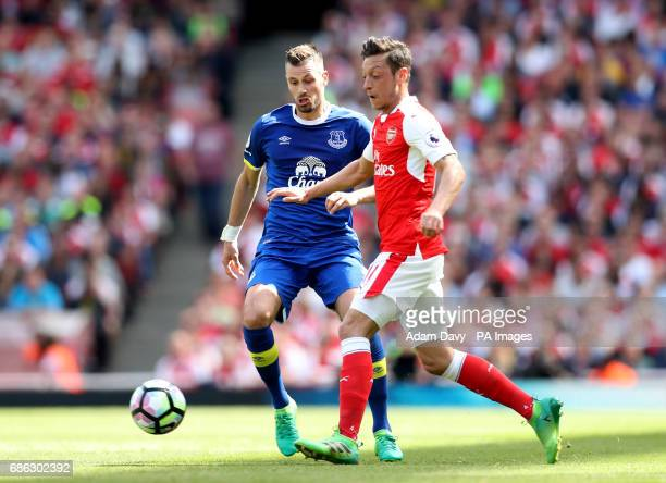 Arsenal's Mesut Ozil and Everton's Morgan Schneiderlin battle for the ball during the Premier League match at the Emirates Stadium London