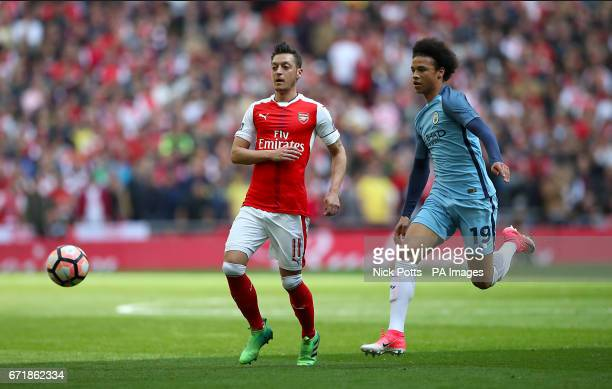 Arsenal's Mesut Ozil and Manchester City's Leroy Sane battle for the ball during the Emirates FA Cup Semi Final match at Wembley Stadium London