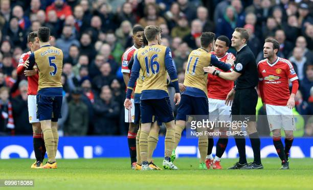 Arsenal's Mesut Ozil and Manchester United's Memphis Depay confront one another