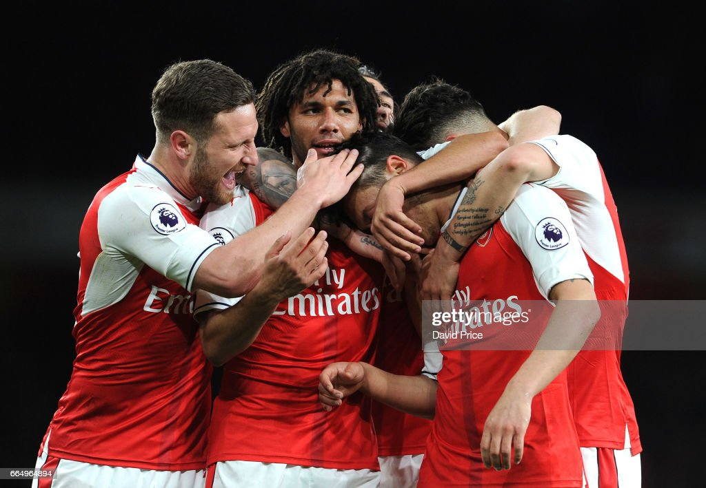 Arsenal's Mesut Ozil celebrates scoring a goal for Arsenal with Mohamed Elneny and Shkodran Mustafi during the Premier League match between Arsenal and West Ham United at Emirates Stadium on April 5, 2017 in London, England.