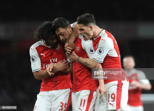 Arsenal's Mesut Ozil celebrates scoring a goal for Arsenal with Mohamed Elneny and Granit Xhaka during the Premier League match between Arsenal and...